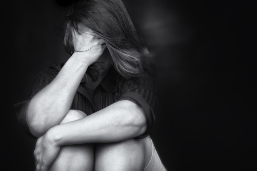 Black and white image of a young woman crying and covering her f
